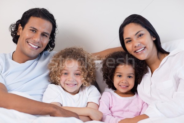 Feliz sorridente família sessão cama juntos Foto stock © wavebreak_media