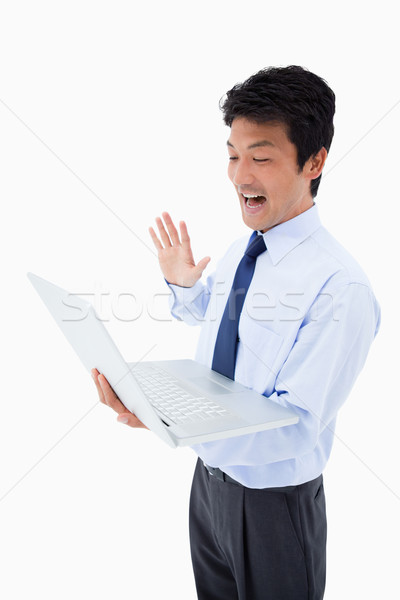Portrait of a businessman waving at a notebook against a white background Stock photo © wavebreak_media