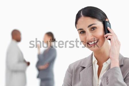 Sonriendo vendedora teléfono móvil colegas detrás blanco Foto stock © wavebreak_media