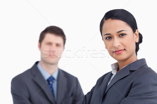 Close up of confident saleswoman with co-worker behind her against a white background Stock photo © wavebreak_media