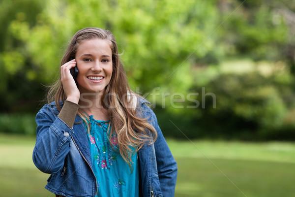 улыбаясь подростку мобильного телефона Постоянный парка трава Сток-фото © wavebreak_media
