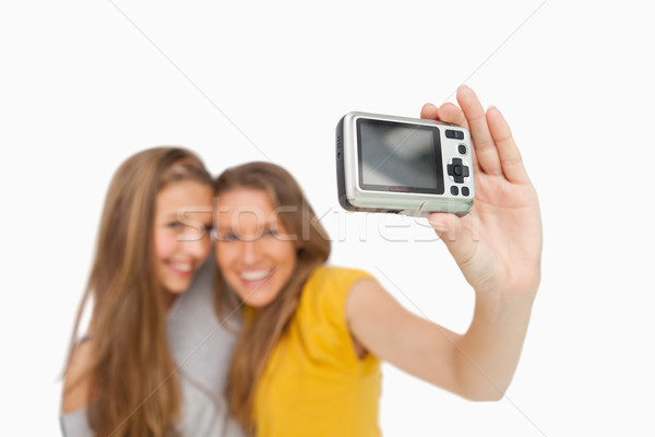 Two students taking a picture of themselves with a digital camera against white background Stock photo © wavebreak_media