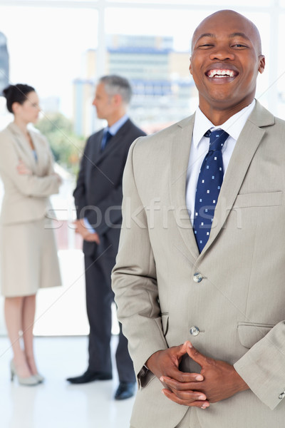 Young executive laughing while standing upright and crossing his hands Stock photo © wavebreak_media