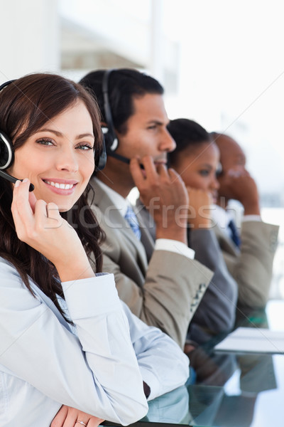 Young smiling call centre agent looking at the camera while working hard Stock photo © wavebreak_media