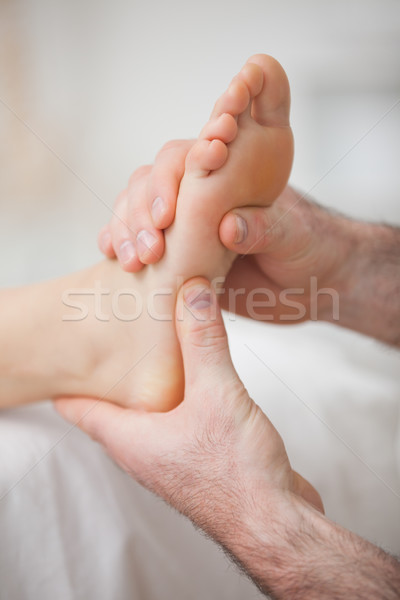 Foot receiving a massage by a physiotherapist in a medical room Stock photo © wavebreak_media