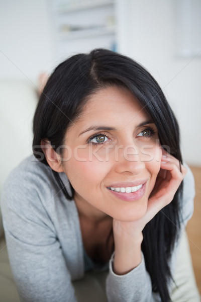 Woman smiling as she holds her head with her palm in a living room Stock photo © wavebreak_media