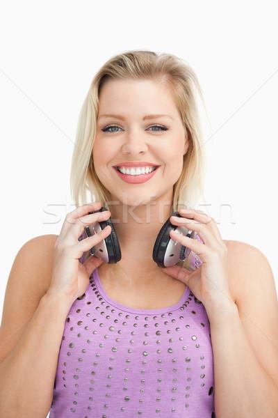 Fair-haired woman holding her headphones against a white background Stock photo © wavebreak_media