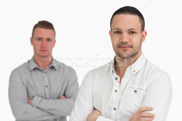 Two men standing while crossing their arms against a white background Stock photo © wavebreak_media