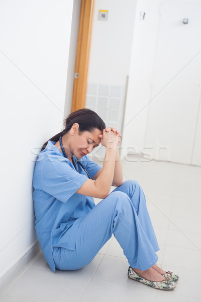 Sad nurse sitting on the floor in hospital ward Stock photo © wavebreak_media