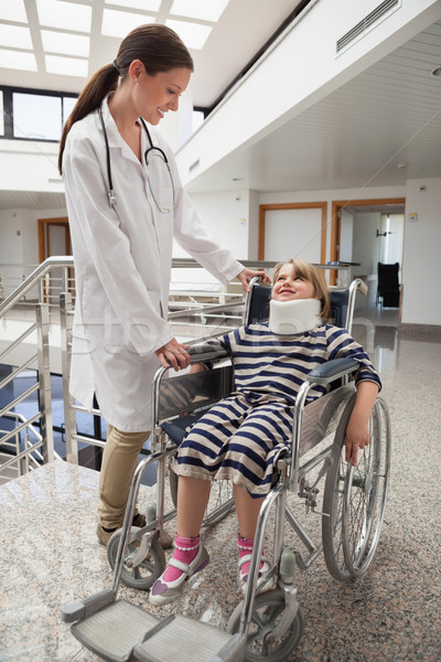 Female doctor smiling at child in wheelchair and neck brace in hospital corridor Stock photo © wavebreak_media