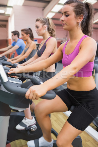 Group of people on exercise bicycles in the gym Stock photo © wavebreak_media
