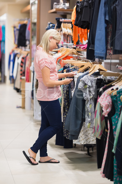 Woman standing in a shop searching for clothes Stock photo © wavebreak_media
