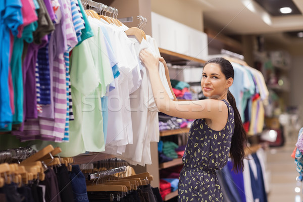 Woman sorting clothes on rail in clothes shop Stock photo © wavebreak_media