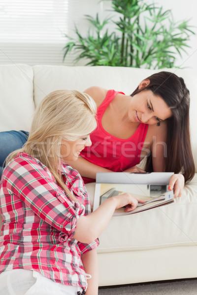 Mulher sessão casa olhando catálogo amigo Foto stock © wavebreak_media