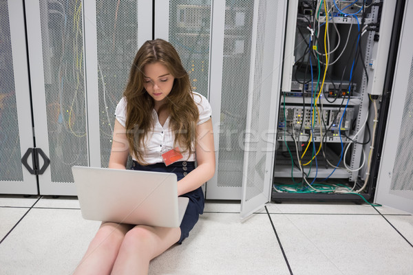 Woman working on servers with laptop sitting on the floor in data center Stock photo © wavebreak_media