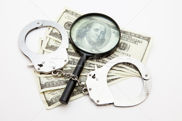 Magnifying glass dollars and handcuffs lying against white background Stock photo © wavebreak_media