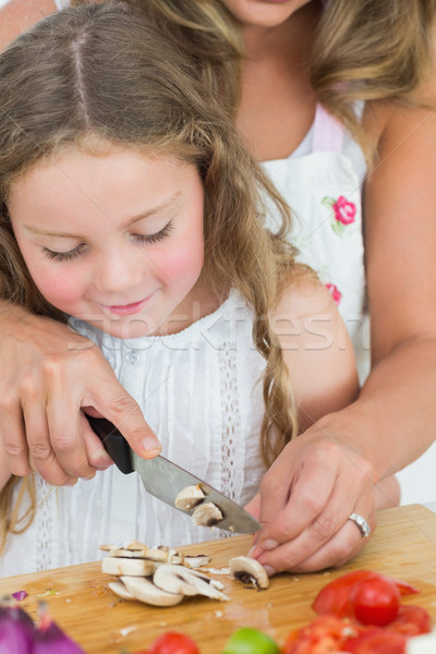 Daughter cutting mushrooms with help from mother Stock photo © wavebreak_media