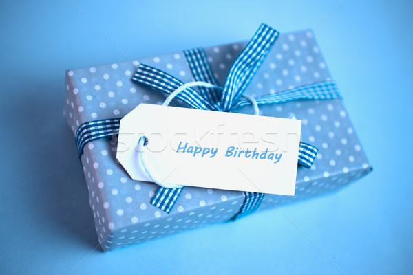 Pretty blue gift with a happy birthday card on a blue background Stock photo © wavebreak_media