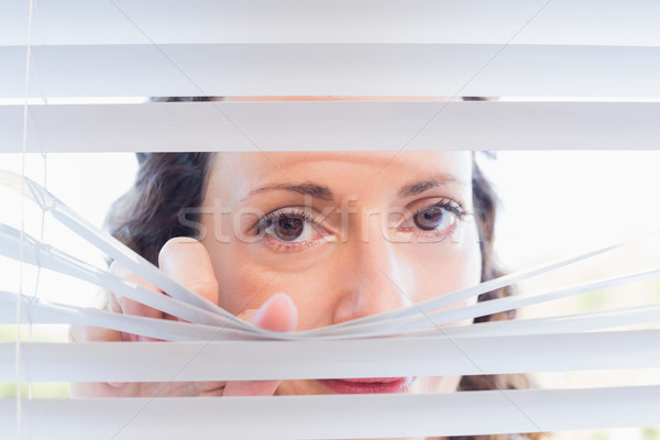 Curious woman looking through blinds Stock photo © wavebreak_media