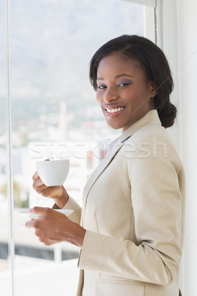 Elegant smiling businesswoman with a cup of tea in office Stock photo © wavebreak_media
