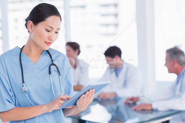 Cirurgião digital comprimido grupo em torno de tabela Foto stock © wavebreak_media