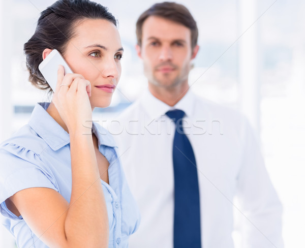 Woman on call with colleague in background at office Stock photo © wavebreak_media