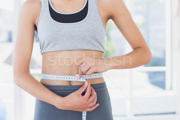 Mid section of a woman measuring waist in fitness studio Stock photo © wavebreak_media
