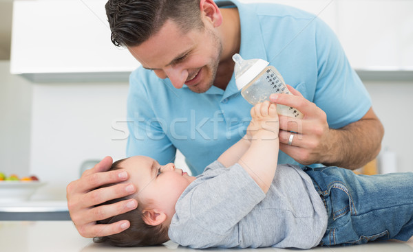 Caring father feeding milk to baby Stock photo © wavebreak_media