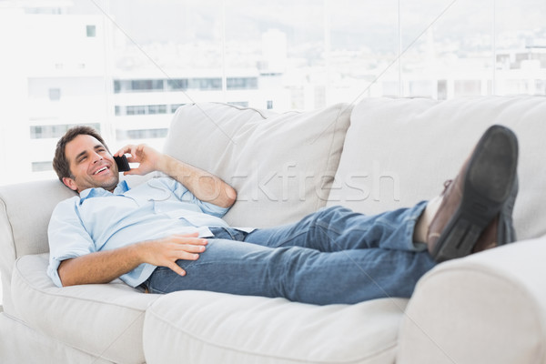 Happy man lying on the couch talking on the phone Stock photo © wavebreak_media
