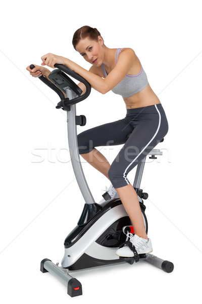 Side view of a beautiful young woman on stationary bike Stock photo © wavebreak_media
