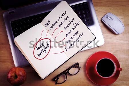 Overhead of open notebook on laptop Stock photo © wavebreak_media