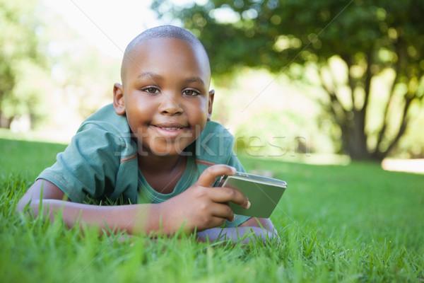 Little boy lying on grass holding digital camera smiling at came Stock photo © wavebreak_media