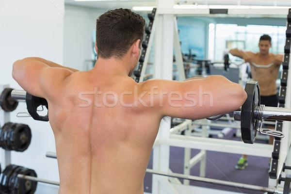 Shirtless focused bodybuilder lifting heavy barbell weight looki Stock photo © wavebreak_media