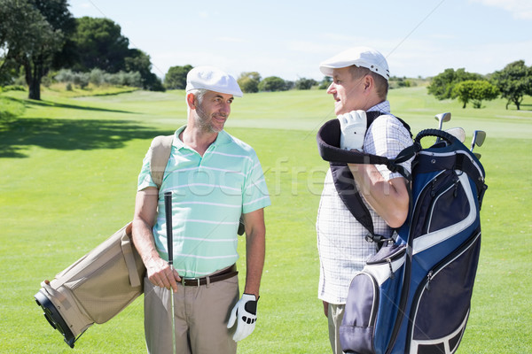 Golfer friends chatting and holding their golf bags Stock photo © wavebreak_media