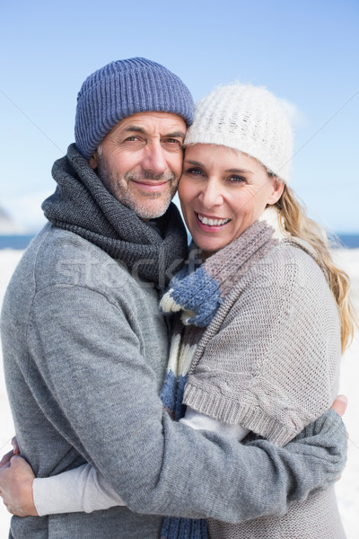 Attractive couple smiling at camera on the beach in warm clothin Stock photo © wavebreak_media