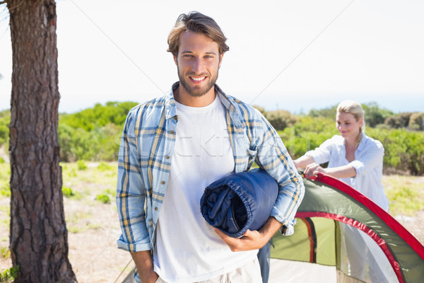 Attractive man smiling at camera while partner pitches tent Stock photo © wavebreak_media