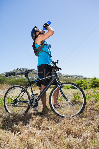 Fit cyclist riding in the countryside taking a drink Stock photo © wavebreak_media