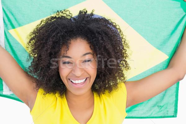 Pretty girl in yellow tshirt holding brazilian flag smiling at c Stock photo © wavebreak_media