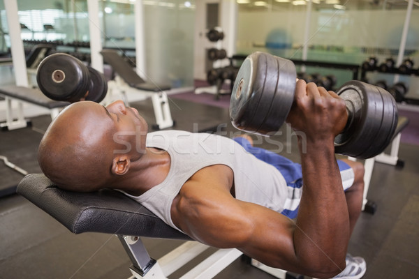 Muscular man exercising with dumbbells Stock photo © wavebreak_media