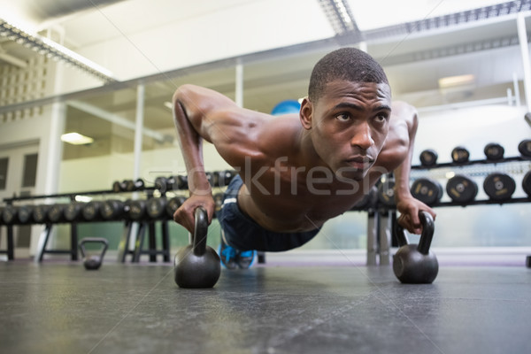 Determined man doing push ups with kettle bells in gym Stock photo © wavebreak_media