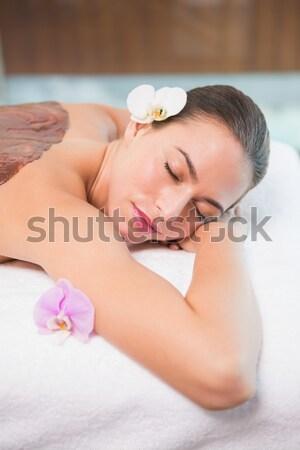 Stock photo: Beautiful woman lying on massage table at spa center
