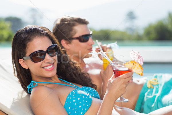Young couple with drinks by swimming pool Stock photo © wavebreak_media