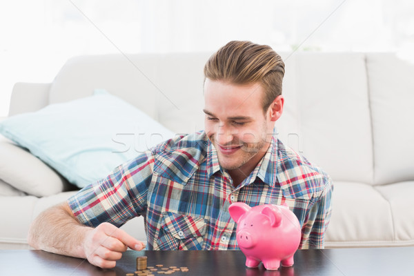 A smiling man holding a pennie Stock photo © wavebreak_media