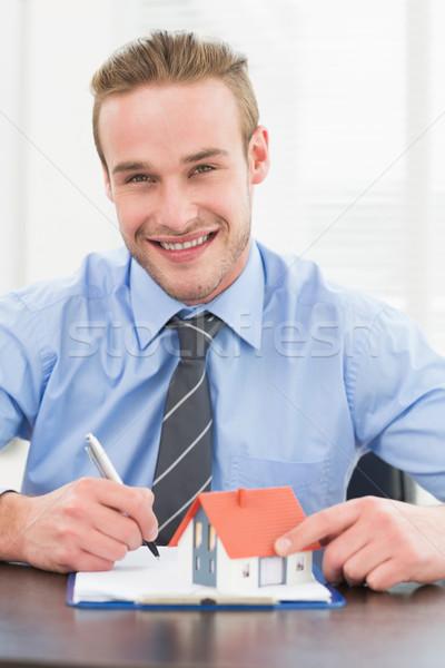 Mosolyog üzletember jegyzetel tart miniatűr otthon Stock fotó © wavebreak_media