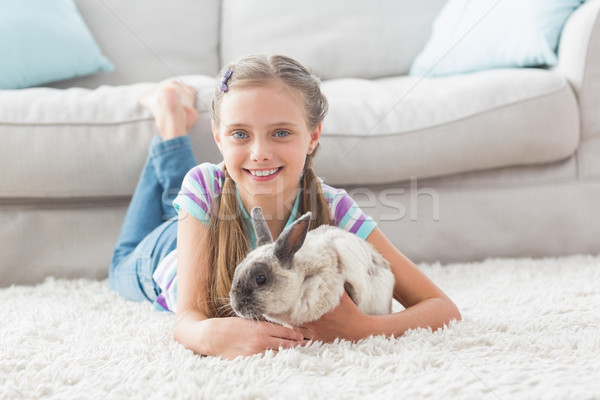 Happy girl with rabbit lying on rug in living room Stock photo © wavebreak_media