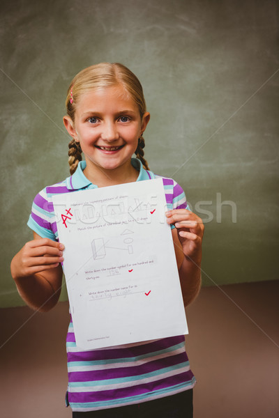 Portrait of cute little girl holding paper Stock photo © wavebreak_media