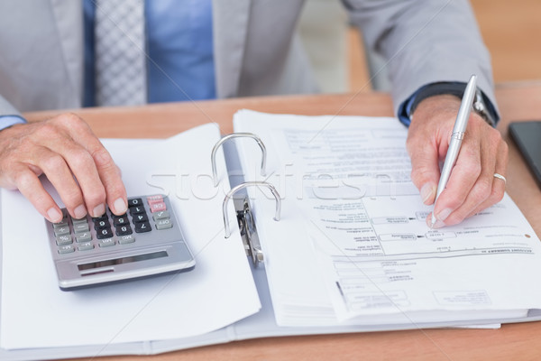 Businessman using calculator to calculate finance  Stock photo © wavebreak_media
