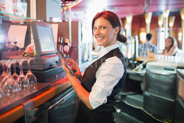 Pretty barmaid using touchscreen till  Stock photo © wavebreak_media