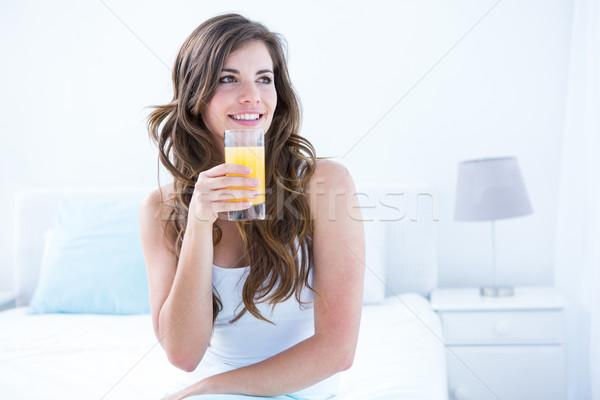 Thoughtful brunette drinking a glass of orange juice  Stock photo © wavebreak_media