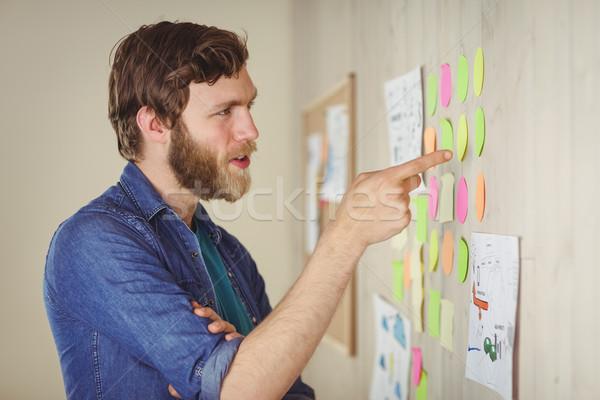 Szakállas hipszter néz ötletelés fal iroda Stock fotó © wavebreak_media